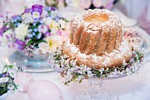 Festively decorated bundt cake on cake stand and centrepiece on Easter table