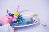 Eine Tasse Cappuccino, Blumengesteck und Petit Four