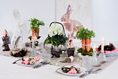 Decorative flower arrangements and rabbit figurines on festively set Easter table