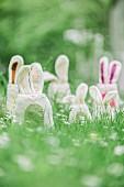 Whimsical felt bunnies hidden amongst grass