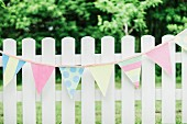 Pastel bunting hung on white picket fence