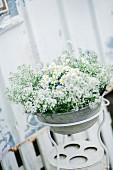 Alte Waschschale im Ständer mit weißen Blumen