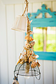 Lamp with wire basket as lampshade and decorated with shells