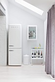 Retro fridge next to drinks trolley in white kitchen