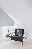 Black armchair with patterned scatter cushion under sloping ceiling