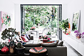 Leather furniture, console table and lowboard with house plants in the living room, view of the green terrace