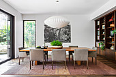 Gray upholstered chairs around large dining table on mottled carpet