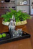 Black tray with carafe and water glasses on the table