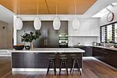 Modern open kitchen with dark wooden fronts and kitchen island