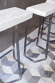 Rustic barstools made of metal and rough wood on old tiled floor
