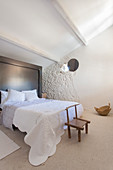 Small wooden chair at foot of bed in bedroom with sloping ceiling