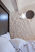 Tiny round window in stone wall with round cover