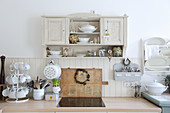Old wall-mounted cabinet above worksurface in country-house kitchen