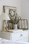Table lamp, old window and vintage ornaments on chest of drawers