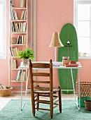 Einfaches Leiterregal für Bücher an apricotfarbener Wand neben angelehntem grünem Surfbrett, davor filigraner Schreibtischplatz mit rustikalem Holzstuhl
