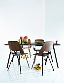 Black dining table, wooden shell chairs and colourful crockery