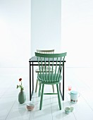 Mint-green wooden chair at black table and retro crockery arranged on white floor