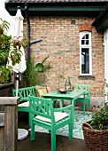 Grüne Gartenmöbel auf der Terrasse vor dem Backsteinhaus
