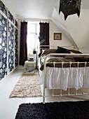 Weißes Metallbett im schwarz-weißen Schlafzimmer unter dem Dach