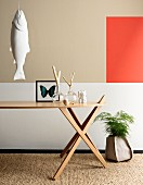 Ornaments on designer table, fish sculpture hung on wall and accent of colour on wall