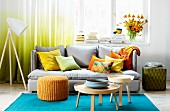 Colourful living room with turquoise rug, grey couch and scatter cushions in yellow and orange