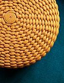 Geflochtener, gelb-orangefarbener Sitzpouf