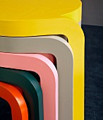 Legs of stacked nest of tables in bright, plain colours