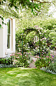 Round arch with climbing roses on the corner of the house in the garden
