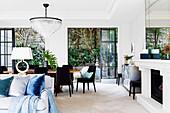 Luxuriöser Wohnraum mit großem Esstisch vor offenen Terrassentüren