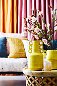 Yellow vases with branches of magnolia on the coffee table