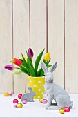 Easter arrangement of concrete rabbit ornament and vase of multicoloured tulips