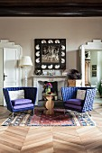 Two purple armchairs and side table in front of open fireplace