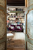 View into library through antique, painted, panelled doors
