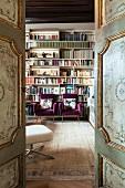 Blick durch antike bemalte Kassettentüren in die Bibliothek