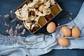 Eggs and cardboard box on blue surface