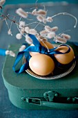 Eggs and blue satin ribbon on pewter plate on top of miniature suitcase