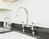 A mixer tap on a glossy black granite kitchen worktop