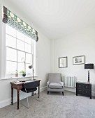 A study with a gray carpet, an armchair and an antique desk