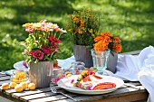 Colourful table set with tagetes and zinnias in the garden