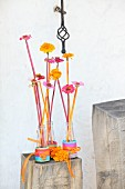 Flowers in Campari bottles on wooden block