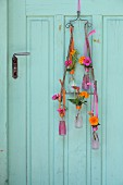 Flower arrangement in Campari bottles hung from vintage door