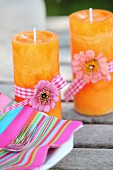 Pink striped napkins and two orange candles decorated with flowers nd ribbons