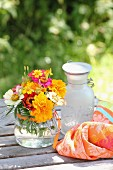 Colourful posies of zinnias and tagetes on garden table