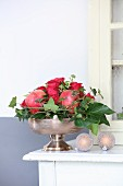 Festive Christmas arrangement of roses, pomegranates and ivy tendrils in silver dish