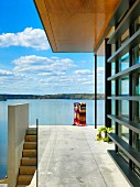Terrace with concrete floor, glass balustrade and view of lake