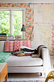 Fish-shaped cushions on sofa against floral wallpaper