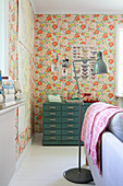 Industrial-style lamp and chest of drawers against floral wallpaper