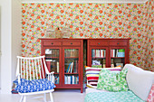 Colourful mixture of patterns in living room with floral wallpaper