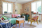 Colourful, eclectic mixture of furniture in living room with floral wallpaper