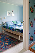 Retro bed linen on bed in bedroom decorated in shades of blue